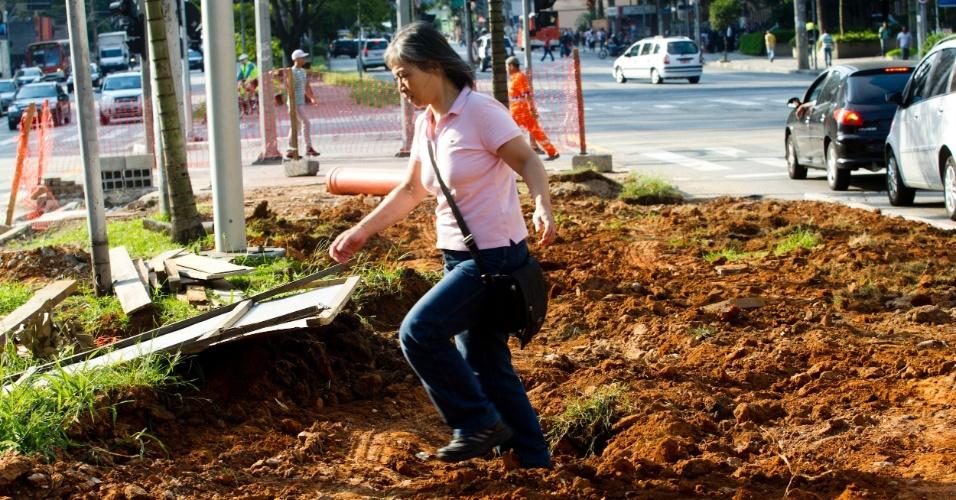 Mulher caminha em meio às obras na avenida Brigadeiro Faria Lima, na zona oeste da capital paulista