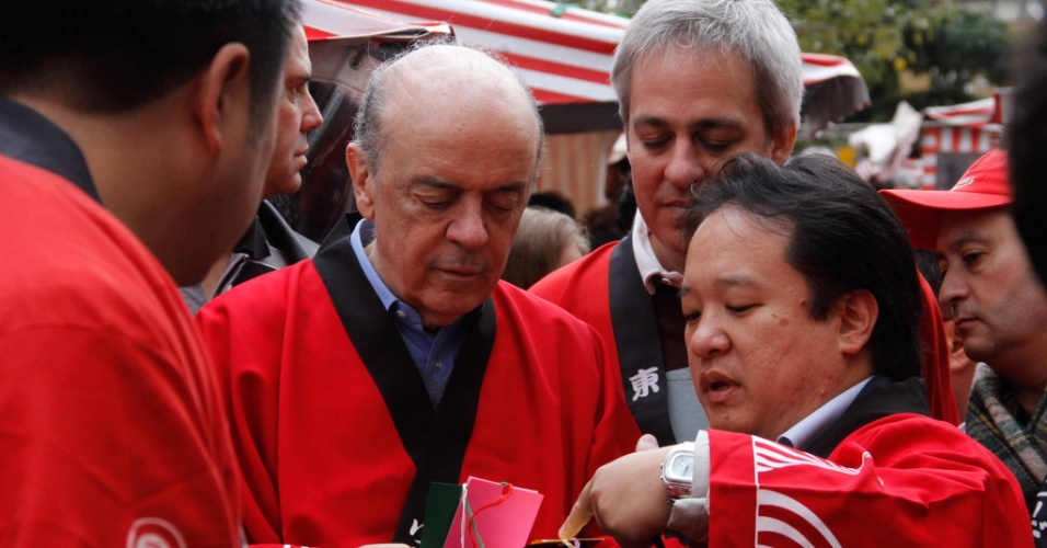 8.jul.2012 - Jos&#233; Serra (&#224; esq.), candidato &#224; Prefeitura de S&#227;o Paulo pelo PSDB, e seu vice Alexandre Schneider (centro) participam de festival de cultura japonesa durante caminhada na Liberdade, bairro que tem forte presen&#231;a da comunidade oriental na cidade 