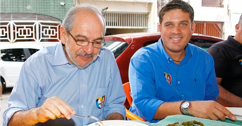 16.jul.2012 - O candidato do PMDB &#224; Prefeitura de Salvador, M&#225;rio Kert&#233;sz (&#224; esq.), experimenta um prato de cozido durante visita &#224; festa popular no bairro da Ribeira, acompanhado do presidente do Esporte Clube Bahia, Marcelo Guimar&#227;es Filho (&#224; dir.)