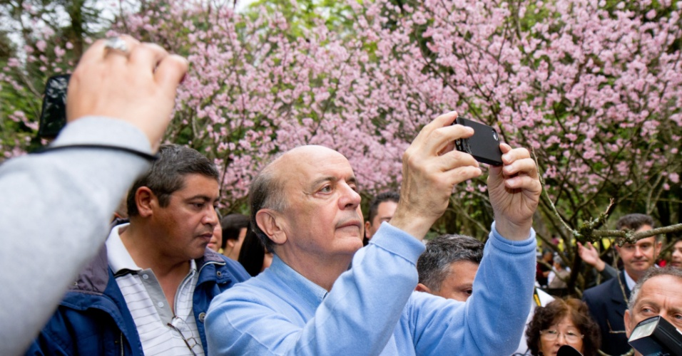 Jos&#233; Serra, candidato do PSDB &#224; Prefeitura de S&#227;o Paulo, usa celular para tirar foto durante a Festa das Cerejeiras, realizada no parque do Carmo (zona leste da capital paulista)