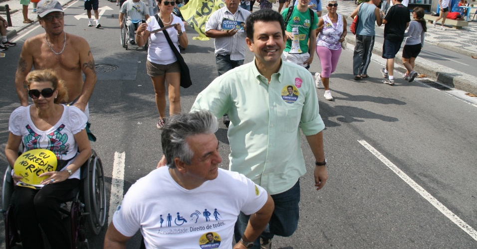 5.ago.2012 - O candidato do PSDB &#224; Prefeitura do Rio de Janeiro, Ot&#225;vio Leite (de camisa verde), faz caminhada pela orla de Ipanema, na zona sul da capital fluminense