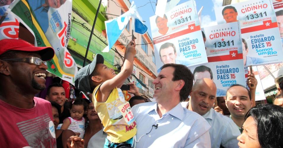 19.ago.2012 - O prefeito e candidato à reeleição, Eduardo Paes (PMDB), carrega uma criança durante caminhada, neste domingo, no Complexo do Alemão, zona norte da cidade