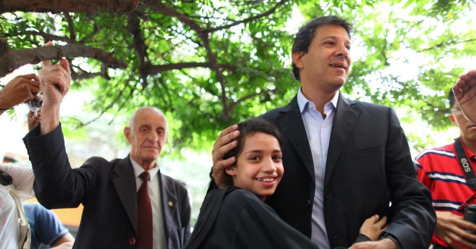 13.set.2012 - O candidato à prefeitura de São Paulo Fernando Haddad (PT) abraça uma criança durante visita a prédios ocupados no centro da cidade por movimentos populares