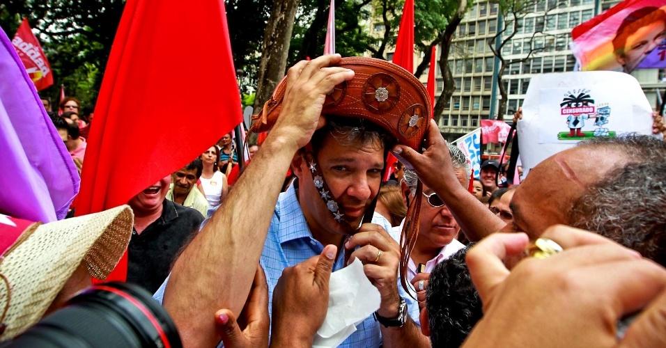 5.out.2012 - Candidato do PT à Prefeitura de São Paulo, Fernando Haddad, fez uma caminhada no centro de São Paulo. Um dos militantes deu um chapéu para o petista colocar