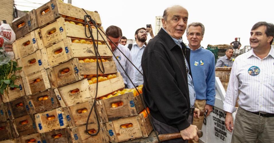 5.out.2012 - O candidato do PSDB à Prefeitura de São Paulo, José Serra, puxa um carrinho de mão carregado com caixas de laranja, durante visita à Ceagesp (Companhia de Entrepostos e Armazéns Gerais de São Paulo)