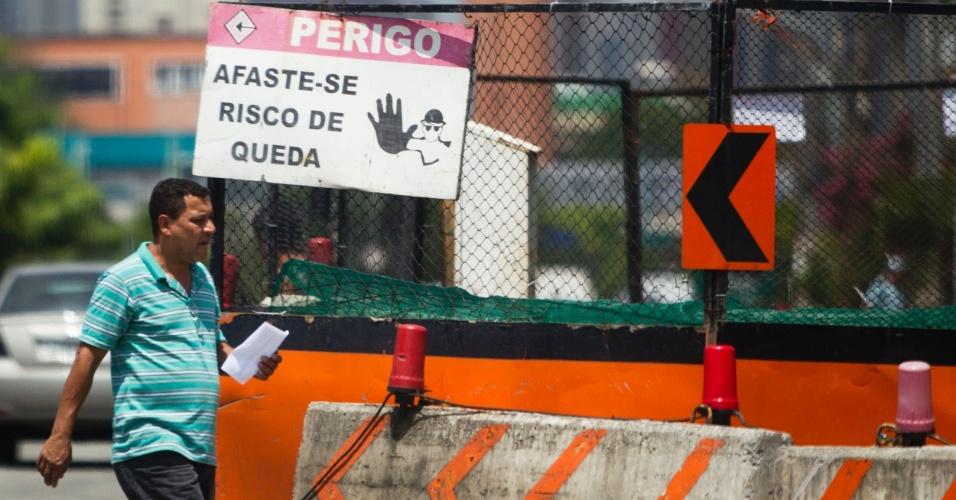 Pedestre passa em frente a placa indicando perigo próximo às obras na avenida Ricardo Jafet, na zona sul de São Paulo