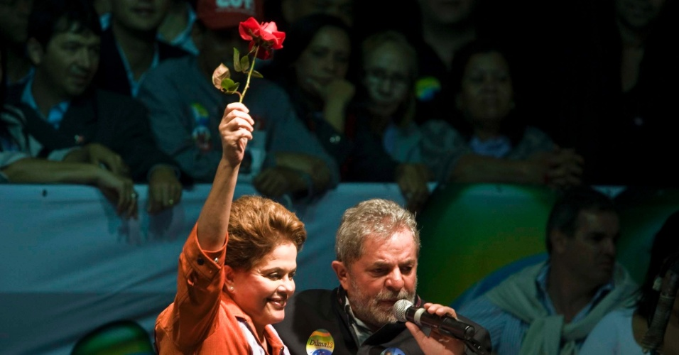 candidata à presidência da República, Dilma Rousseff (PT) levanta rosa dada pelo presidente Luiz Inácio Lula da Silva durante comício em Belo Horizonte (MG)