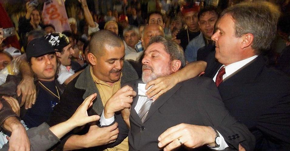o candidato Luiz Inácio Lula da Silva é agarrado por simpatizantes ao chegar a comício no Largo da Alfândega em Florianópolis (SC)