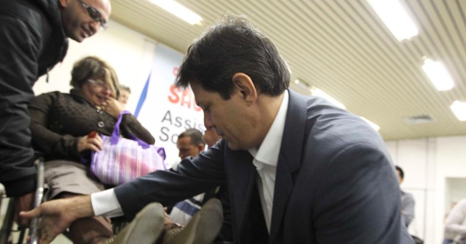 20.mai.2012 - O pré-candidato do PT à Prefeitura de São Paulo, Fernando Haddad, ajuda ajuda a colocar palestrante que usa cadeira de rodas em cima de palco durante seminário em São Paulo neste sábado (19)