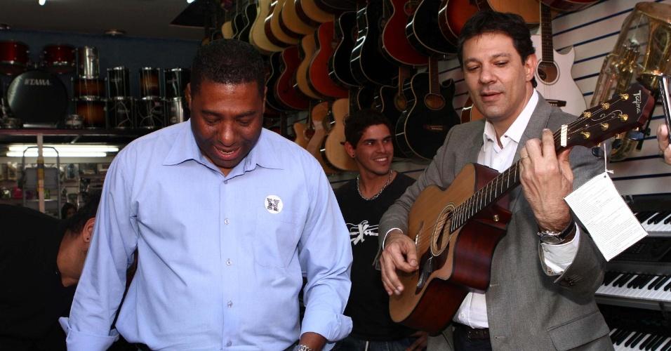 10.jul.2012 - Fernando Haddad, candidato do PT à Prefeitura de São Paulo, toca violão com o vereador Netinho de Paula durante caminhada pelo bairro de São Miguel Paulista, zona leste da capital