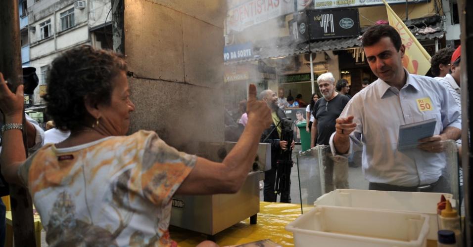 12.jul.2012 - Marcelo Freixo, candidato do PSOL à Prefeitura do Rio de Janeiro, cumprimenta comerciante durante visita à favela da Rocinha