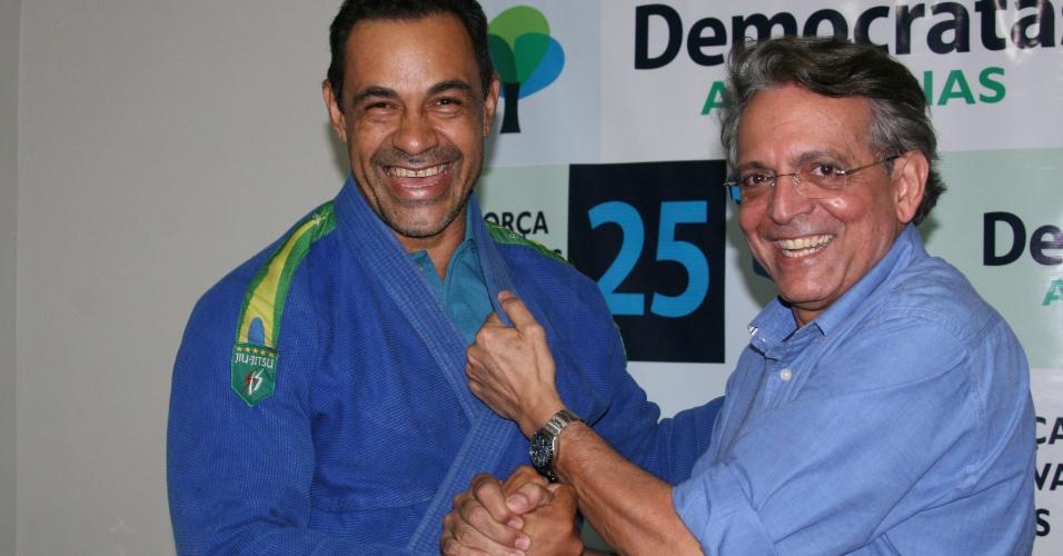 12.jul.2012 - O candidato do DEM à Prefeitura de Manaus, Pauderney Avelino, simula posição de jiu-jitsu com o lutador e campeão brasileiro da modalidade, Allan Farias