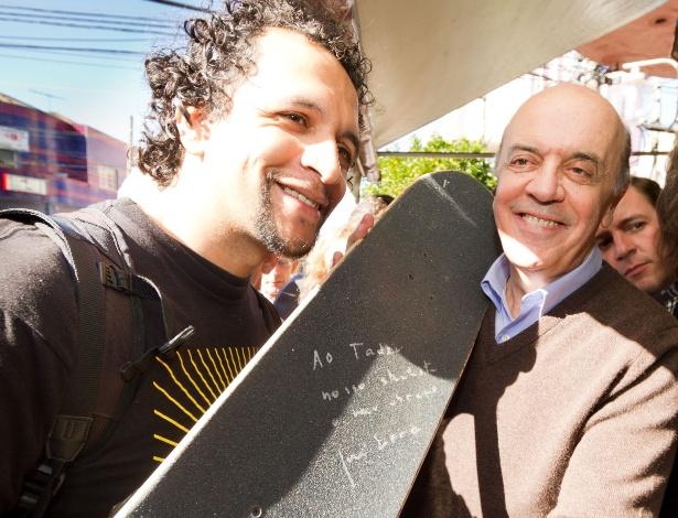 13.jul.2012 - José Serra, candidato do PSDB à Prefeitura de São Paulo, autografa um skate durante visita ao Mercado Municipal do Ipiranga, na zona sul