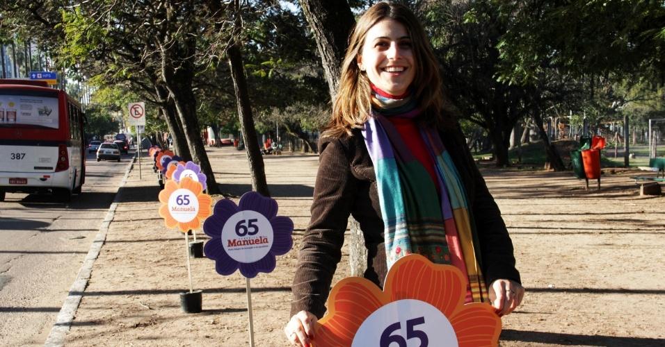 13.jul.2012 - Manuela D'Ávila, candidata do PC do B à Prefeitura de Porto Alegre, espalha placas de campanha no formato de vasos com flores no parque da Redenção, nesta sexta-feira (13)