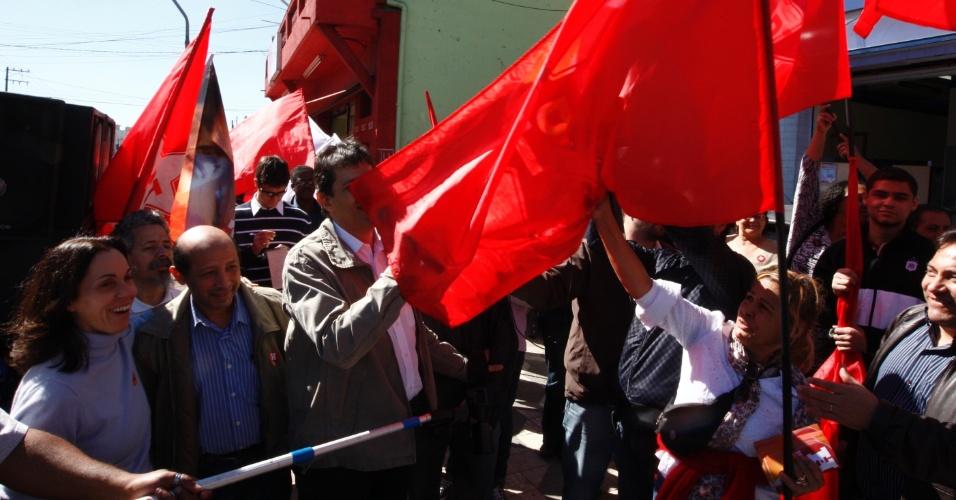 13.jul.2012 - O candidato do PT à Prefeitura de São Paulo, Fernando Haddad, se enrosca com bandeira do PT durante discurso em caminhada pelo Campo Limpo, zona sul da capital paulista, nesta sexta-feira (13)