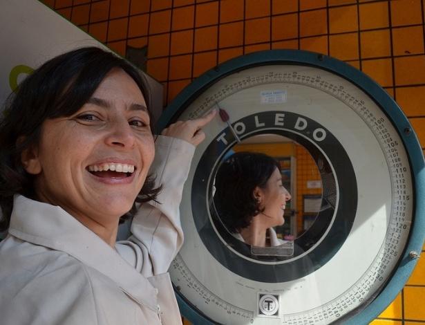 14.jul.2012 - Soninha Francine, candidata do PPS à Prefeitura de São Paulo, se pesa em uma balança antiga de uma farmácia durante pausa em caminhada no jardim São Luiz, zona sul de São Paulo, neste sábado