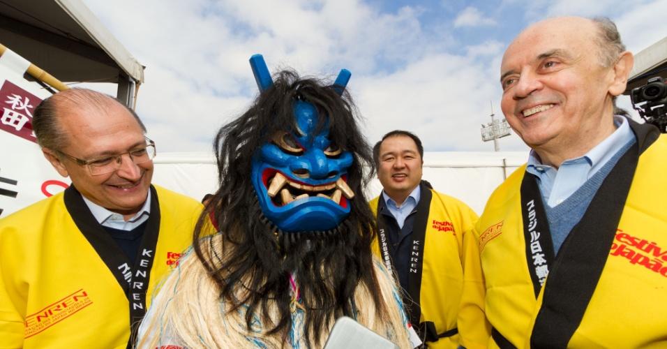 15.jul.2012 - José Serra (à direita), participa do 15º Festival do Japão, no Centro de Exposições Imigrantes, zona sul da capital paulista, junto com o governador Geraldo Alckmin (à esquerda), neste domingo. Na imagem, os tucanos posam ao lado de personagem floclórico japonês