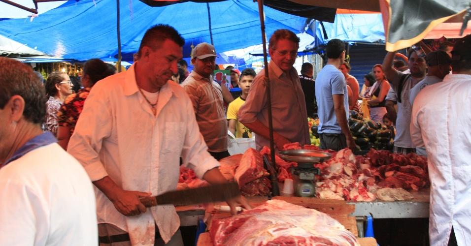 15.jul.2012 - O candidato do DEM à Prefeitura de Manaus, Pauderney Avelino, observa açougueiro durante caminhada pela feira do São José, na manhã deste domingo