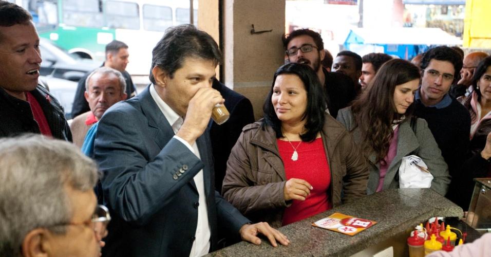 16.jul.2012 - O candidato do PT à Prefeitura de São Paulo, Fernando Haddad, toma um café durante caminhada na avenida Mateo Bei, na zona leste da cidade