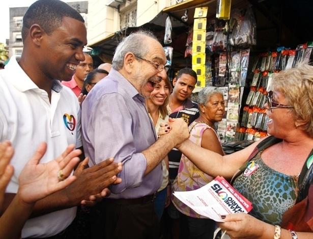19.jul.2012 - O candidato à Prefeitura de Salvador pelo PMDB, Mário Kertész, sorri ao cumprimentar eleitora caminhada pela estação de ônibus da Lapa, nesta quinta-feira (19). Seu vice (à esquerda), Nestor Neto (PMDB), também participa da campanha nas ruas