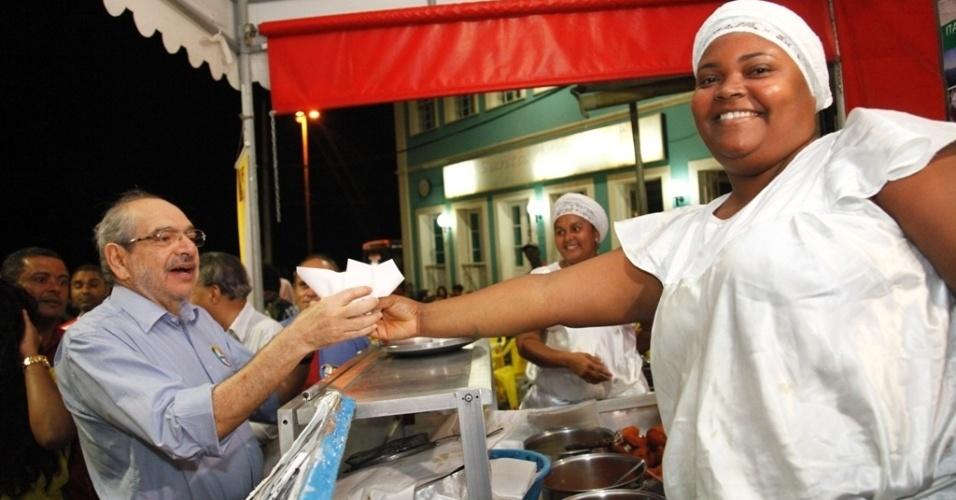 20.jul.2012 - O candidato do PMDB à Prefeitura de Salvador, Mário Kertész, compra um acarajé no Largo de Santana, no bairro do Rio Vermelho, durante caminhada de campanha