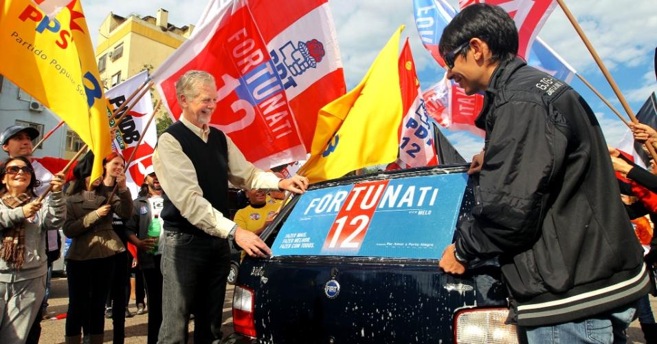 22.jul.2012 - O candidato à reeleição para a Prefeitura de Porto Alegre, José Fortunati (PDT), ajuda a colar um adesivo de sua campanha em um carro, durante evento na manhã deste domingo, no largo Zumbi dos Palmares