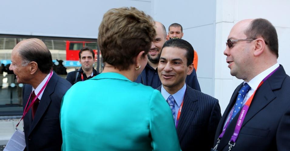 27.jul.2012 - Presidente Dilma Rousseff (de costas) cumprimenta o presidente nacional do PRB, Marcos Pereira (centro), nesta sexta-feira, em Londres. Ela confirmou o pedido ao PRB para não fazer acordos nas eleições municipais, mas disse que foi em tom de brincadeira