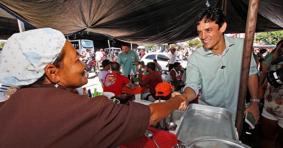 Daniel Coelho, candidato do PSDB à Prefeitura do Recife, cumprimenta vendedora de comida no bairro da Estância, zona sudoeste da capital pernambucana