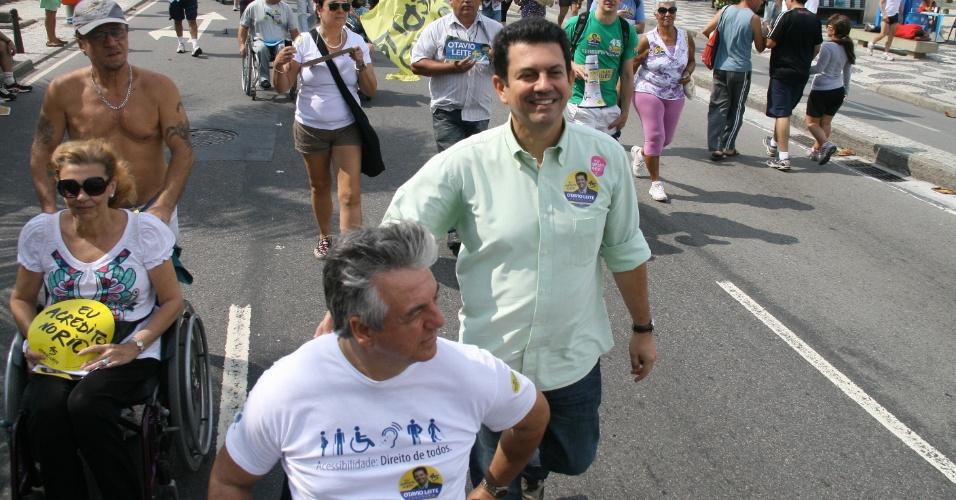 5.ago.2012 - O candidato do PSDB à Prefeitura do Rio de Janeiro, Otávio Leite (de camisa verde), faz caminhada pela orla de Ipanema, na zona sul da capital fluminense