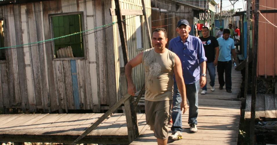 6.ago.2012 - O candidato do DEM à Prefeitura de Manaus, Pauderney Avelino (de camisa azul), caminhou nesta segunda-feira pela Comunidade da Sharp, bairro da da zona leste da capital amazonense