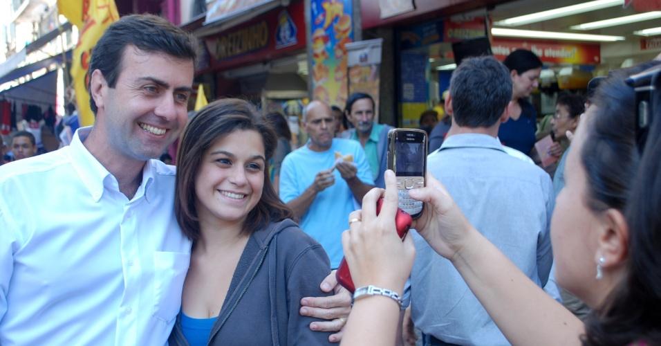 7.ago.2012 - O candidato do PSOL à prefeitura, Marcelo Freixo (PSOL), faz pausa para tirar foto com eleitora durante caminhada com eleitores na região do Saara, área de comércio popular localizada no centro