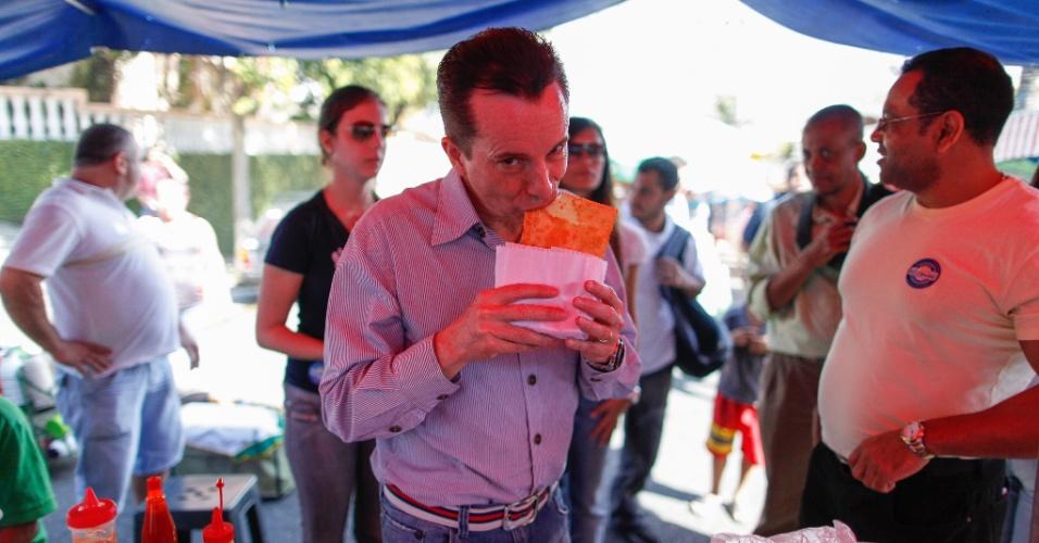 11.ago.2012 - O candidato do PRB à Prefeitura de São Paulo, Celso Russomanno, experimenta pastel durante caminhada em feira livre em Santo Amaro, zona sul da cidade