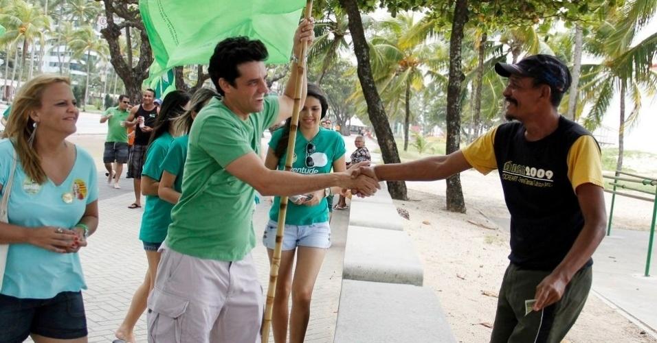 13.ago.2012 - O candidato do PSDB à Prefeitura do Recife, Daniel Coelho (de verde), cumprimenta eleitor durante caminhada pela praia de Boa Viagem na manhã desta segunda-feira