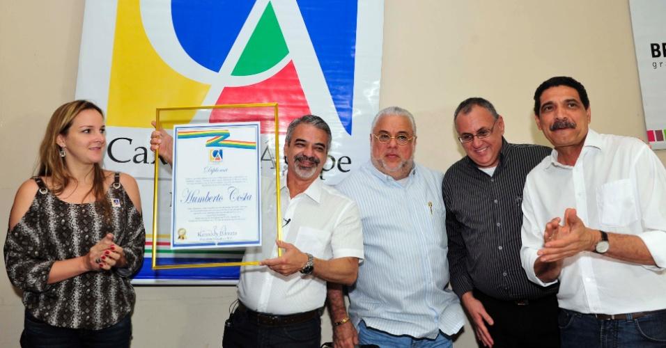 15.ago.2012 - O candidato a prefeito do Recife Humberto Costa (PT) mostra a placa que recebeu de homenagem do Caxangá Ágape, clube social pernambucano, nesta quarta-feira