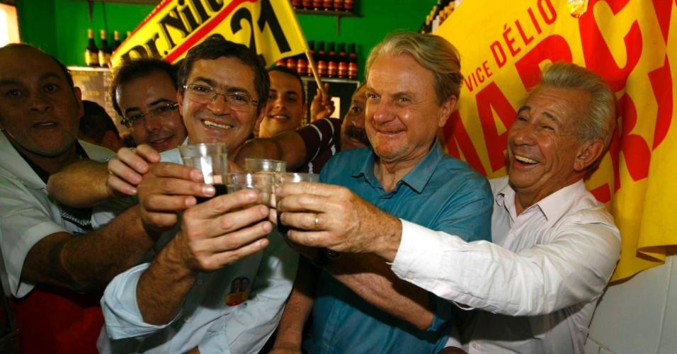 20.ago.2012 - Marcio Lacerda (segundo da dir. para à esq.), candidato à reeleição em Belo Horizonte pelo PSB, toma café em uma padaria do bairro Guarani ao lado do seu vice, Délio Malheiros (terceiro da dir. para à esq.)
