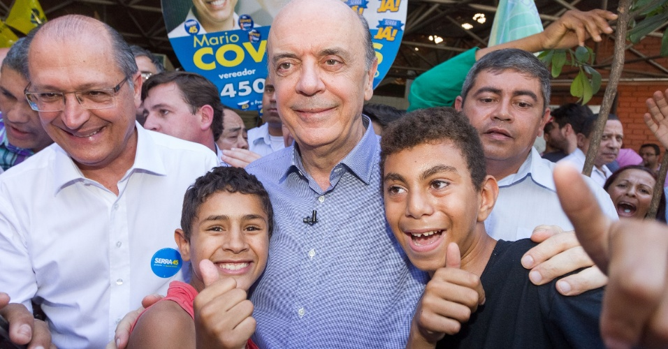 24.ago.2012 - O candidato do PSDB à Prefeitura de São Paulo, José Serra, tira foto com crianças durante caminhada pelo bairro de Guaianazes, na zona leste da capital, ao lado do governador Geraldo Alckmin (de óculos)