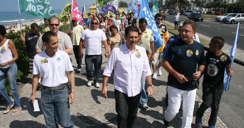 26.ago.2012 - O candidato do PSDB à Prefeitura do Rio, Otavio Leite (centro), caminhou na praia da Barra da Tijuca (zona oeste), acompanhado do senador Álvaro Dias (à dir) e apoiadores