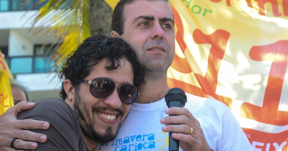 26.ago.2012 - O candidato do PSOL à Prefeitura do Rio de Janeiro, Marcelo Freixo (à dir), abraça o deputado federal Jean Wyllys (à esq) durante caminhada na orla de Ipanema (zona sul), neste domingo (26)