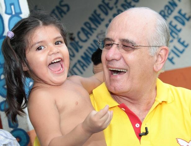 30.ago.2012 - O candidato a prefeito de Manaus Serafim Corrêa (PSB) brinca com uma criança durante caminhada no bairro de Novo Israel, na Zona Leste da cidade