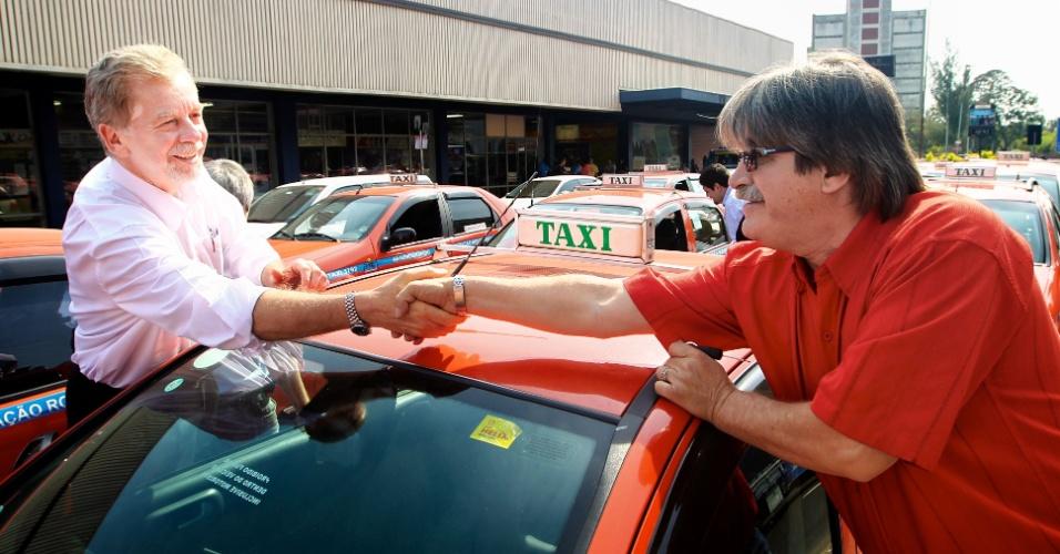 5.set.2012 - José Fortunati (à esq.), candidato à reeleição em Porto Alegre pelo PDT, cumprimenta taxista no ponto da estação rodoviária da capital gaúcha, no bairro de Marcílio Dias