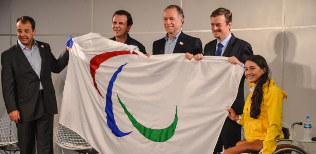 Prefeito do Rio de Janeiro, Eduardo Paes (segundo à esq.) mostra a bandeira paralímpica trazida de Londres
