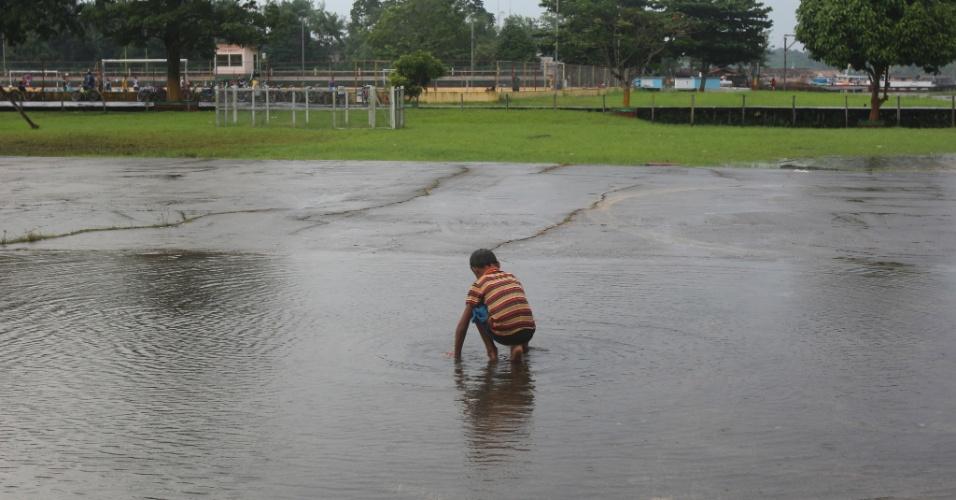 Menino brinca em poça de água da chuva na pista de pouso de Afuá (PA)