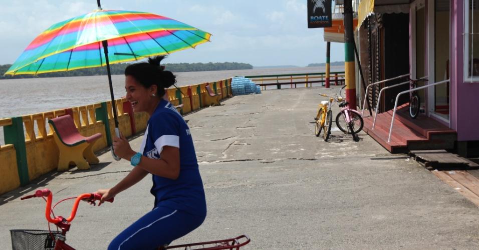 Moradora se protege da alta temperatura com um guarda-sol ao mesmo tempo em que pedala