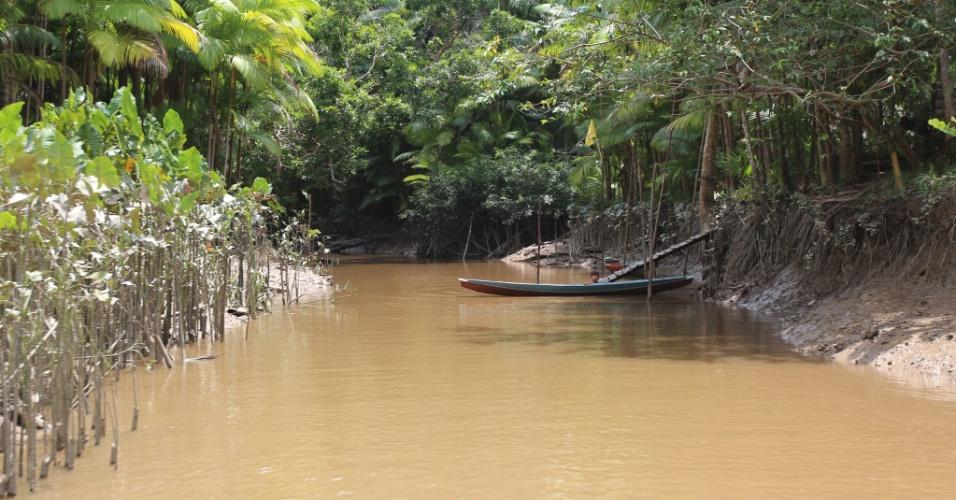 Criança brinca no rio na frente da casa onde mora