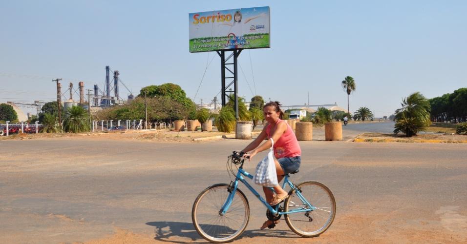 Moradora de Sorriso (MT) atravessa a BR-163, de bicicleta