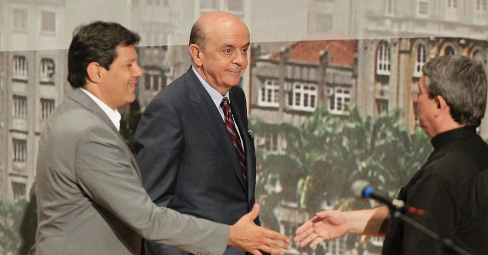 20.set.2012 - Fernado Haddad (à esq.), do PT, e José Serra (centro), do PSDB, cumprimentam o mediador do debate realizado pela Arquidiocese de São Paulo. Celso Russomanno (PRB), que lidera a corrida eleitoral, não compareceu