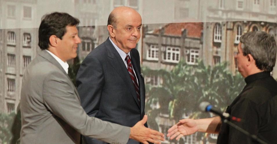 20.set.2012 - Fernado Haddad (à esq.), do PT, e José Serra (centro), do PSDB, cumprimentam o mediador do debate realizado pela Arquidiocese de São Paulo. Celso Russomanno (PRB), que lidera a corrida eleitoral, não compareceu