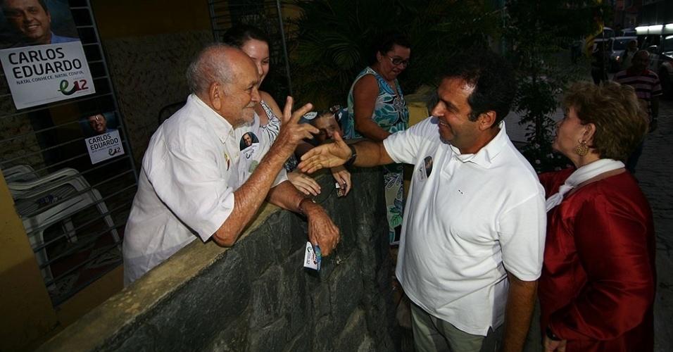 25.set.2012 - O candidato do PDT à Prefeitura de Natal, Carlos Eduardo (à dir., de branco), cumprimenta eleitor ao lado de sua vice, Wilma de Faria (de vermelho), durante caminhada pelo bairro de Nova Descoberta, região sul da capital potiguar