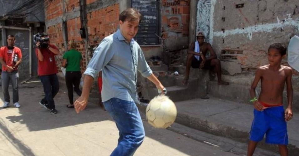 27.set.2012 - O candidato do DEM à Prefeitura do Rio de Janeiro, Rodrigo Maia, joga bola com crianças durante visita a uma creche no morro do Tuiuti, no bairro de São Cristóvão, zona norte da capital