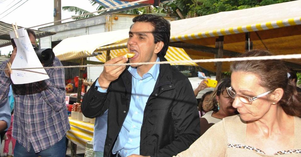 28.set.2012 - O candidato do PMDB à Prefeitura de São Paulo, Gabriel Chalita, come uma laranja durante visita a uma feira livre no Jardim Maringá, zona leste da capital